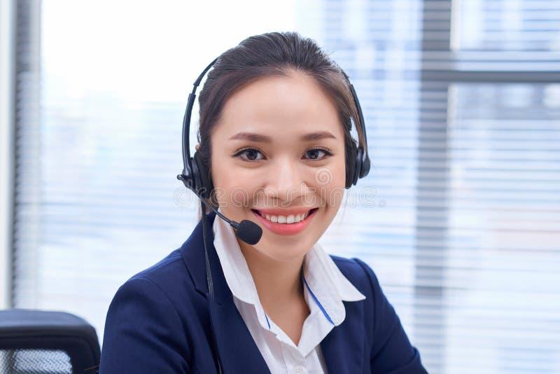 Portrait d'op?rateur f?minin de sourire heureux de t?l?phone de support ? la client?le sur le lieu de travail Asiatique photographie stock