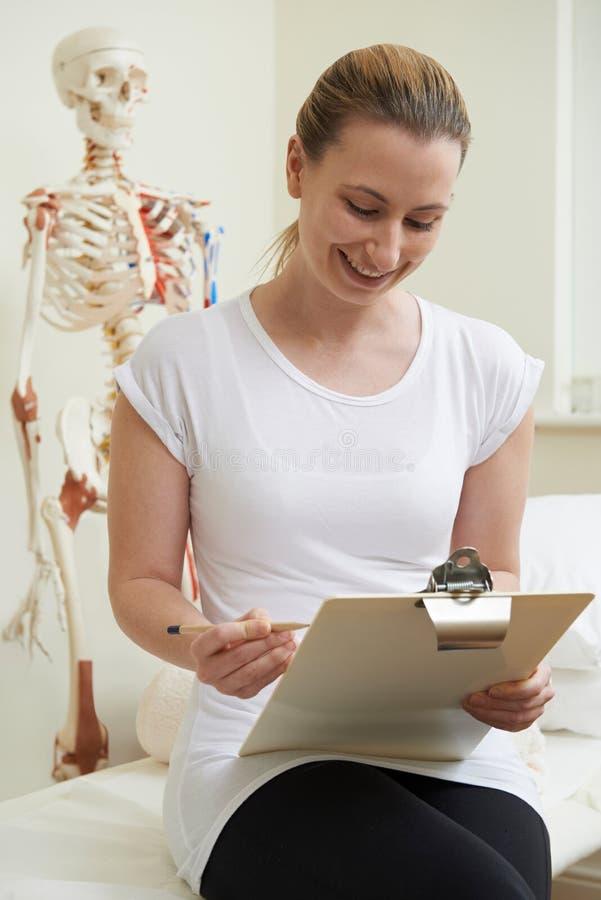 Portrait d'ostéopathe féminin dans la chambre de consultation photos stock