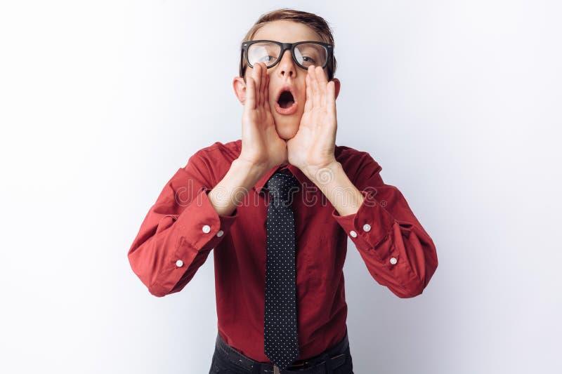 Portrait d'un écolier positif et émotif posant et dépeignant un cri perçant, fond blanc, verres, chemise rouge, thème d'affaires image stock