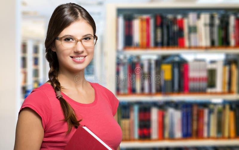 Portrait d'un étudiant dans une bibliothèque image stock