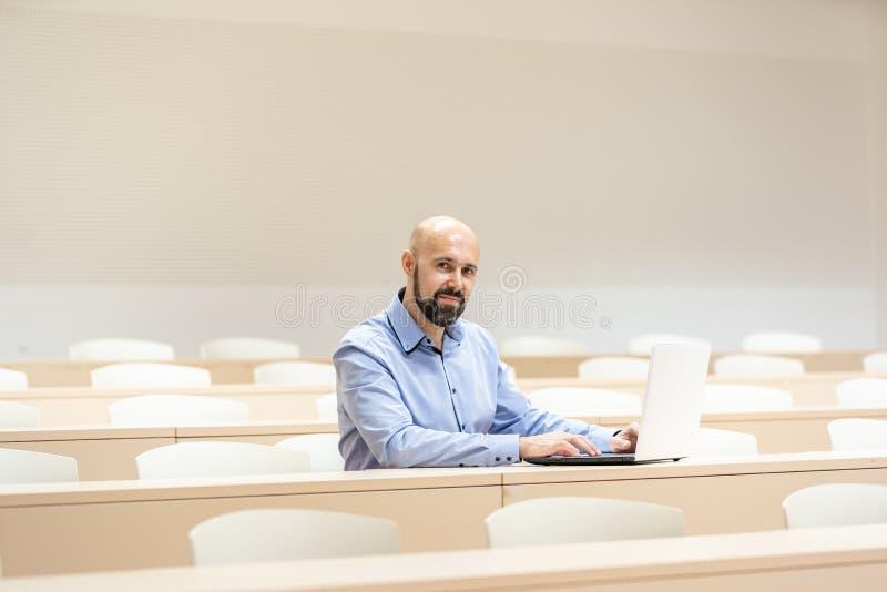 Portrait d'un étudiant masculin heureux utilisant l'ordinateur portable à l'université Préparation aux examens image libre de droits