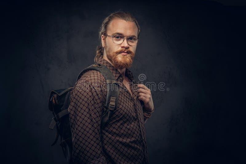 Portrait d'un étudiant roux de hippie en verres habillés dans une chemise brune, prises un sac à dos, posant à un studio photographie stock