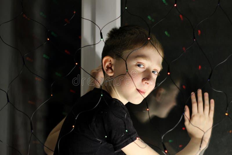 Portrait d'un adolescent à la fenêtre image stock