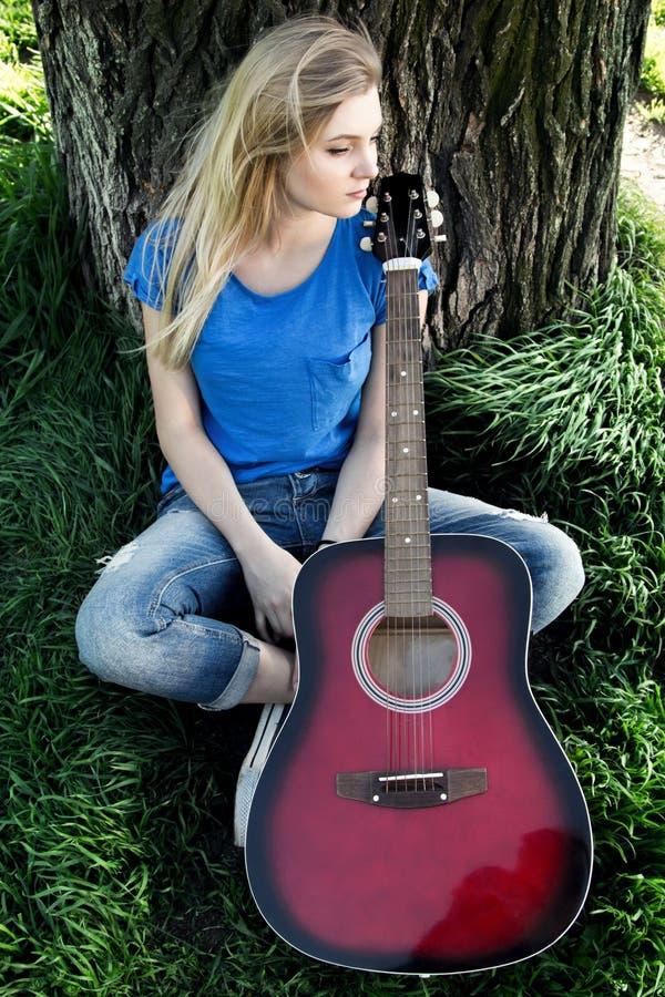 Portrait d'un adolescent avec une guitare en parc photos libres de droits