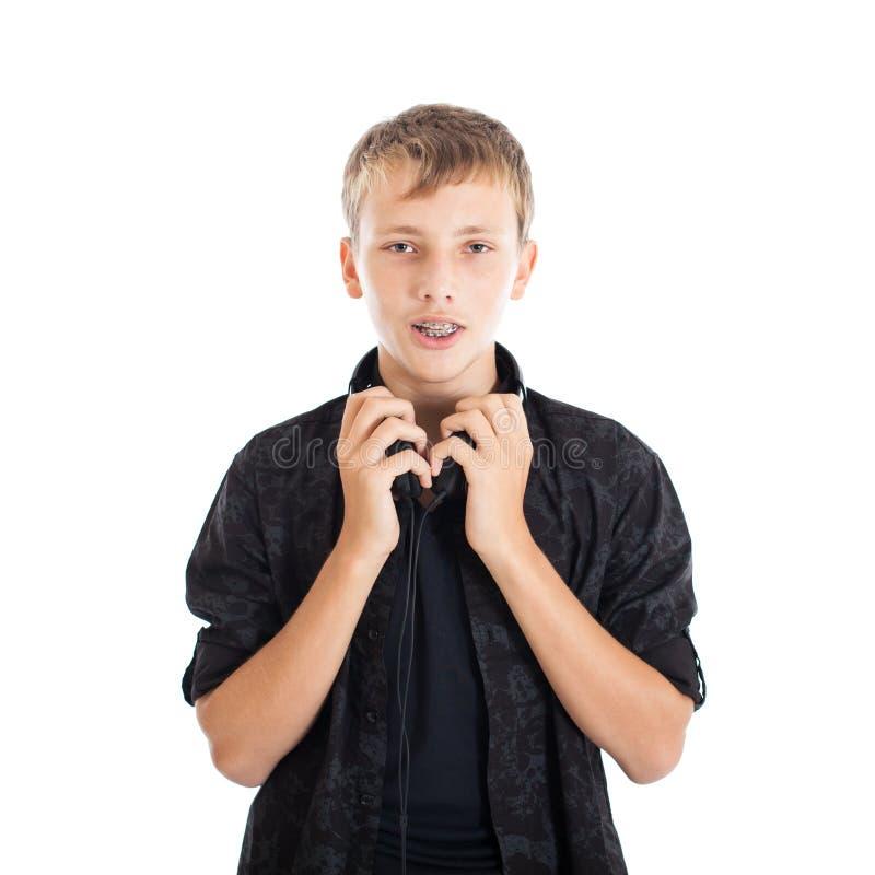 Portrait d'un adolescent mignon avec les écouteurs, croisillons sur des dents photo stock
