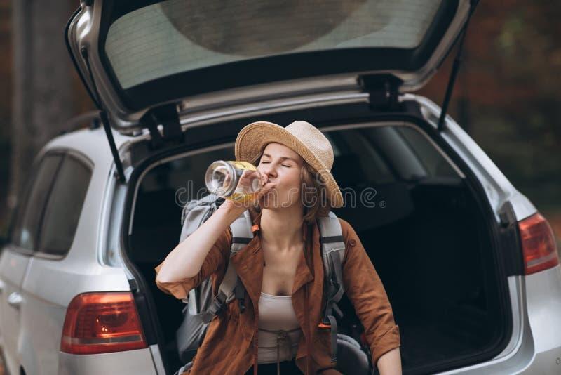 Portrait d'un alcool potable de fille d'une bouteille Belle fille dans un chapeau buvant une bouteille de whiskey photo libre de droits