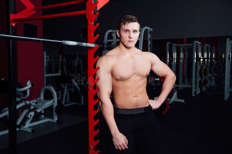 Portrait d'un athlète bel au gymnase l'homme fait l'exercice avec le barbell, la position et l'accroupissement grand sûr image libre de droits