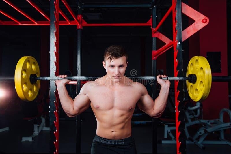 Portrait d'un athlète bel au gymnase l'homme fait l'exercice avec le barbell, la position et l'accroupissement grand sûr photo libre de droits