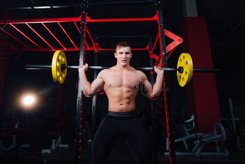 Portrait d'un athlète bel au gymnase l'homme fait l'exercice avec le barbell, la position et l'accroupissement grand sûr photographie stock