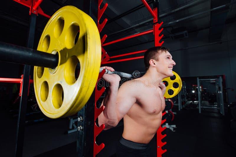 Portrait d'un athlète bel au gymnase l'homme fait l'exercice avec le barbell, la position et l'accroupissement grand sûr images stock