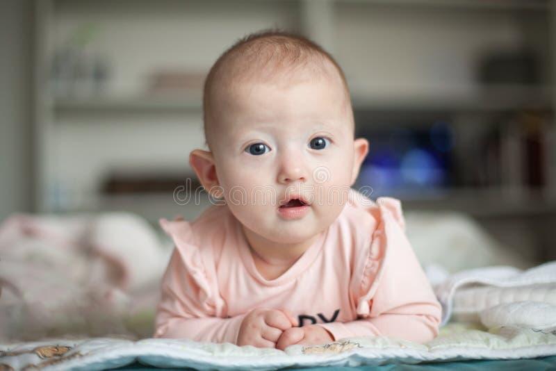 Portrait d'un bébé avec du charme se trouvant sur son estomac Matin de famille ? la maison Temps de ventre photographie stock