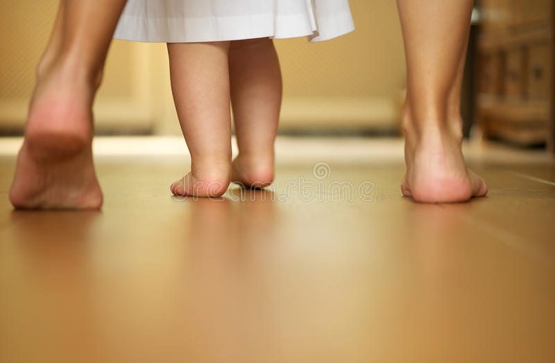 Portrait d'un bébé de enseignement de mère à marcher à l'intérieur photo stock