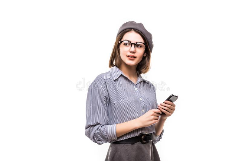 Portrait d'un béret de port de sourire de femme tenant le téléphone portable et regardant loin au-dessus du fond blanc images stock