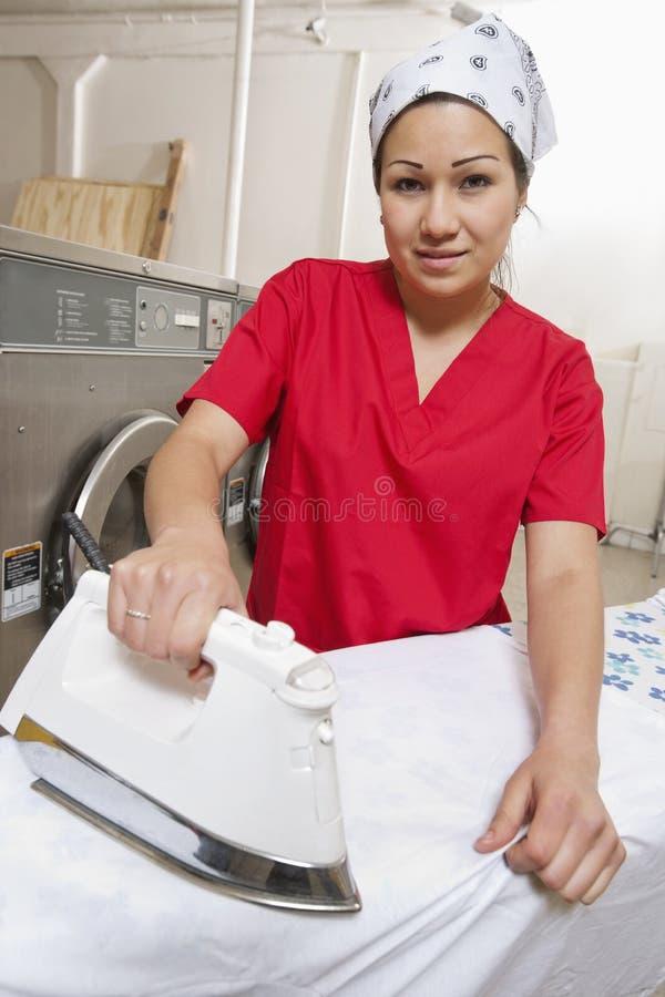 Portrait d'un bandana de port des employés féminins tout en repassant dans la laverie automatique photographie stock libre de droits