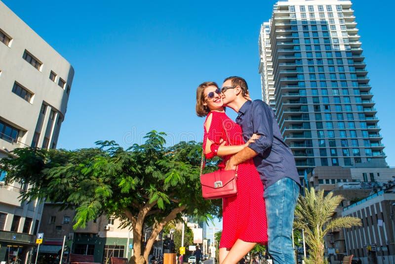 Portrait d'un beau couple dans les vêtements lumineux et des lunettes de soleil embrassant, riant pendant la promenade dans la ru photo libre de droits