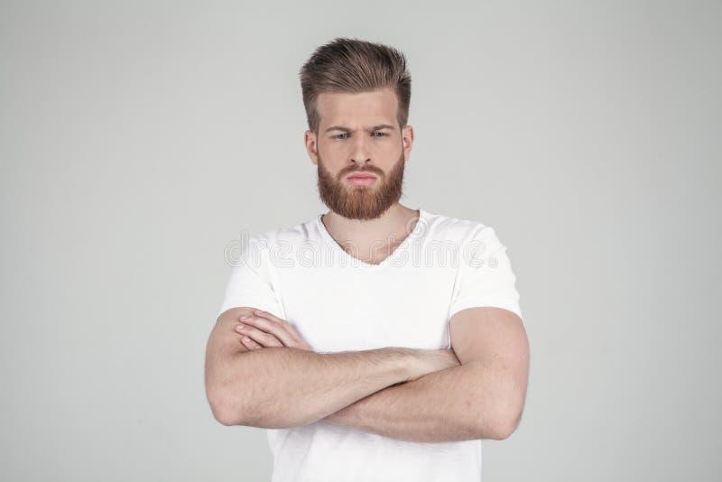 Portrait d'un beau hippie sexy habill? dans un T-shirt blanc les mains de prise ont croisé il se tient bouleversé devant image libre de droits