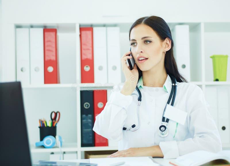 Portrait d'un beau médecin parlant au téléphone dans le bureau photos stock