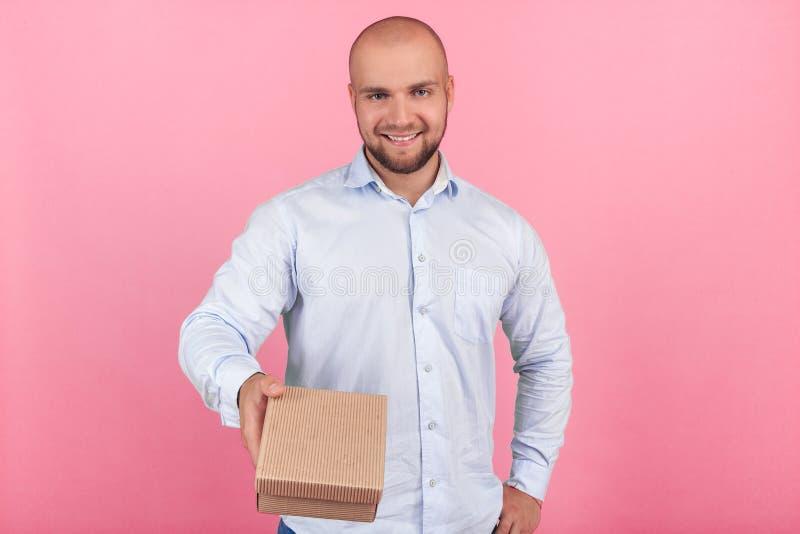 Portrait d'un bel homme chauve avec une barbe habill?e dans une chemise blanche montre un cadeau ? la cam?ra avec des ?motions jo image libre de droits