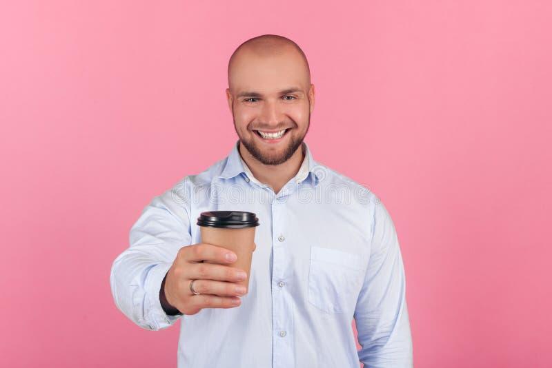 Portrait d'un bel homme chauve avec une barbe habill?e dans une chemise blanche montre une tasse de caf? dans la cam?ra avec des  photo stock