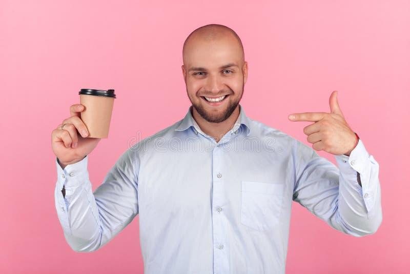 Portrait d'un bel homme chauve avec une barbe habill?e dans une chemise blanche points dans une tasse de caf? avec des ?motions h photos stock