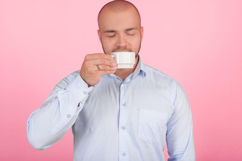 Portrait d'un bel homme chauve avec une barbe habill?e dans une chemise blanche renifle le caf? d'une tasse qui s'est lev?e au ne photo stock