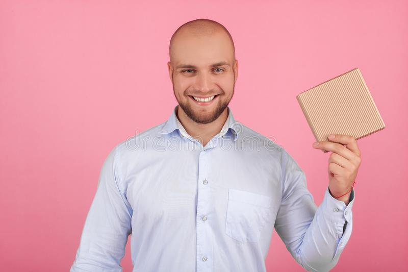 Portrait d'un bel homme chauve avec une barbe habill?e dans une chemise blanche tient un cadeau autour du visage avec des ?motion image stock