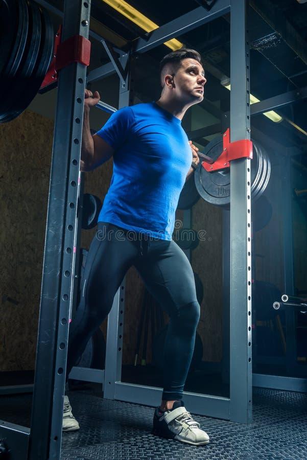 Portrait d'un bodybuilder avec un barbell dans le gymnase pendant le train photos stock