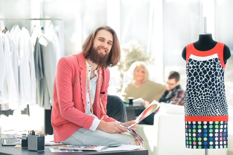 Portrait d'un concepteur d'habillement s'asseyant sur un bureau dans le studio photos stock