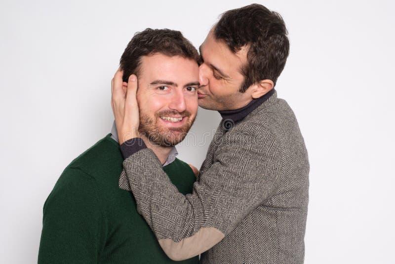 Portrait d'un couple gai d'hommes dans des baisers de studio image libre de droits