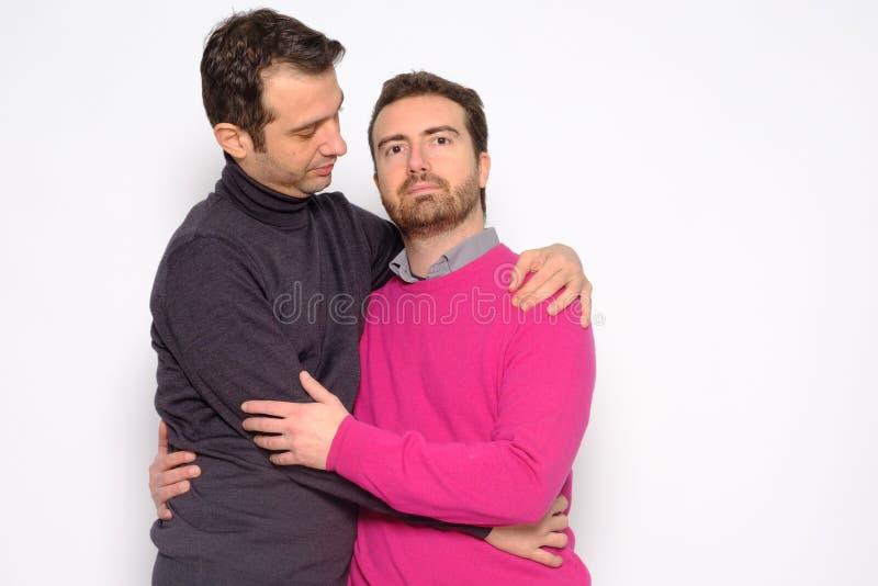 Portrait d'un couple gai d'hommes dans l'embrassement de studio photos stock