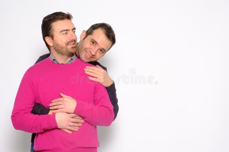 Portrait d'un couple gai d'hommes dans l'embrassement de studio images stock