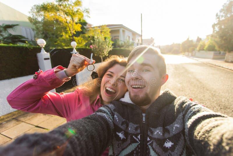 Portrait d'un couple gai riant tenant des clés sur leur nouvelle maison Nouveau concept de propriétaires photographie stock libre de droits
