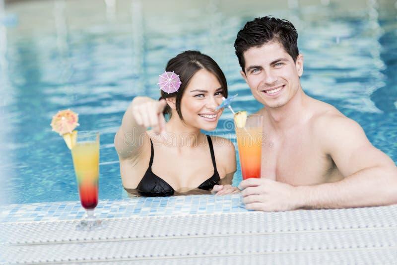Portrait d'un couple souriant et buvant un cocktail dans une piscine image stock