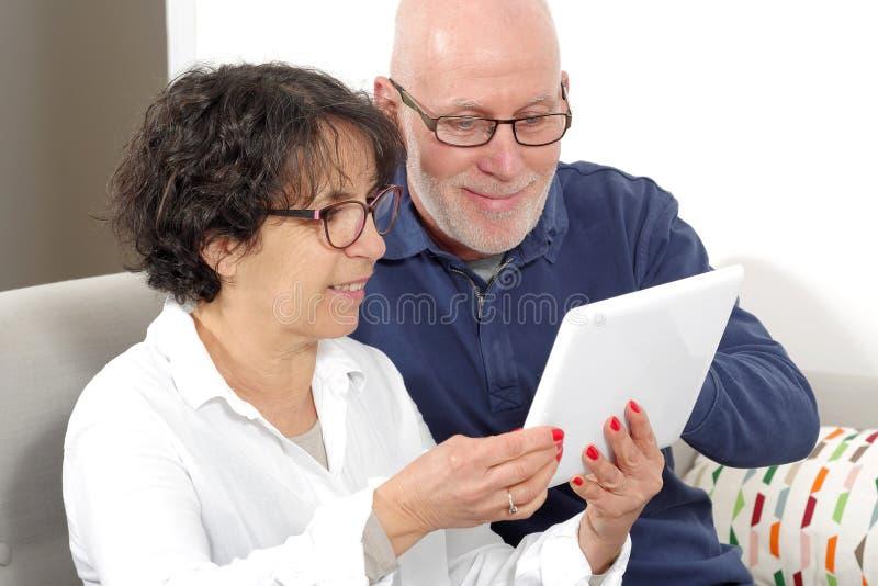 Portrait d'un couple supérieur heureux utilisant le comprimé numérique image stock