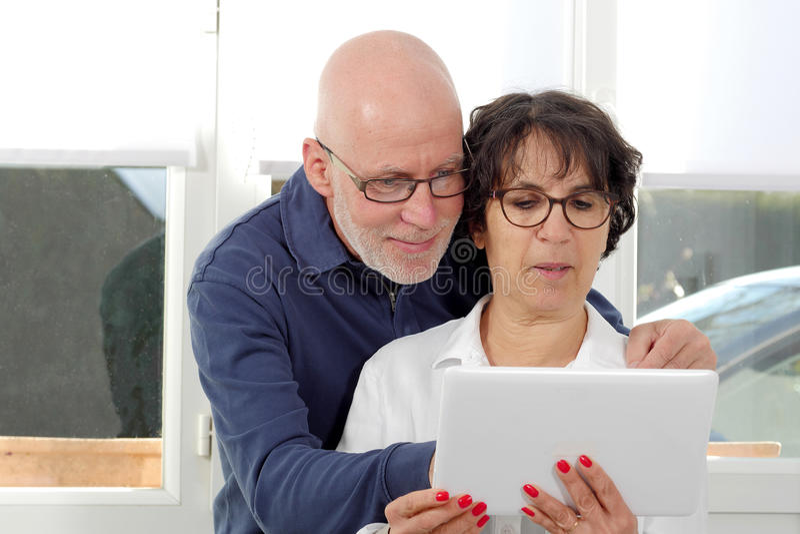 Portrait d'un couple supérieur heureux utilisant le comprimé numérique photo stock