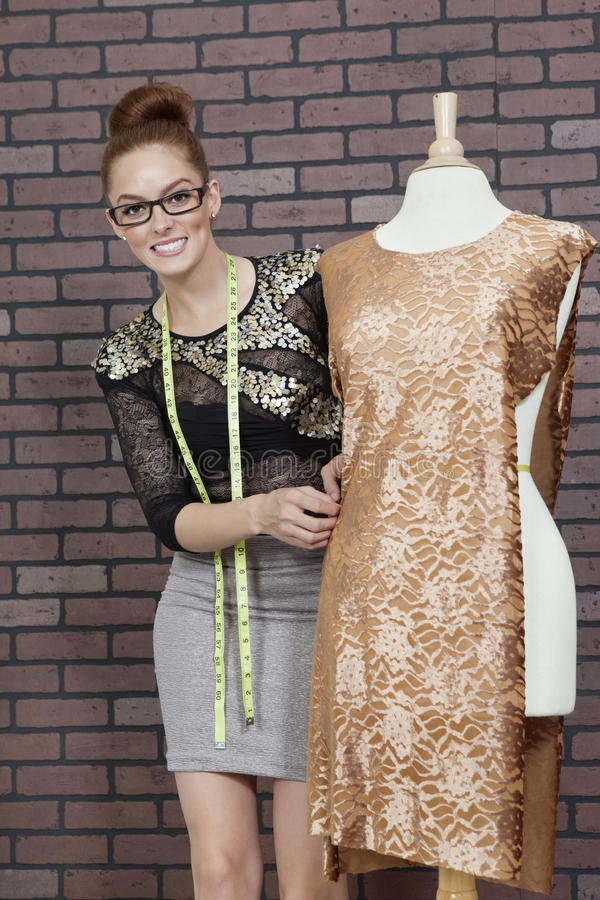 Portrait d'un couturier féminin attirant ajustant le tissu sur le simulacre du tailleur images libres de droits