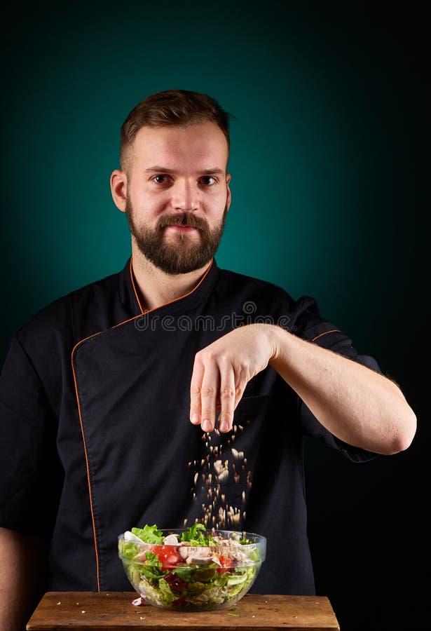 Portrait d'un cuisinier masculin beau de chef faisant la salade savoureuse sur un fond bleu vert brouillé photos stock