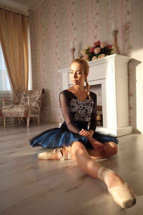 Portrait d'un danseur classique professionnel s'asseyant sur le plancher en bois Ballerine féminine ayant un concept de ballet de photo libre de droits