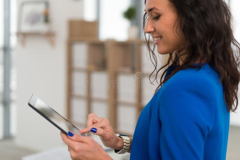 Portrait d'un directeur de bureau tenant son comprimé, dactylographiant, utilisant l'Internet de Wi-Fi et les applications toucha image libre de droits