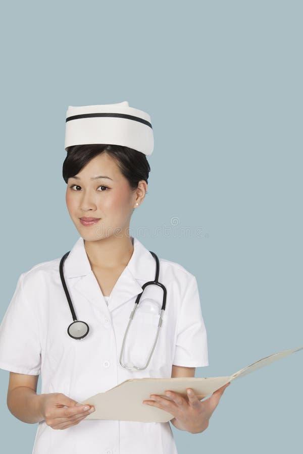 Portrait d'un docteur attirant avec le rapport médical au-dessus du fond bleu-clair images libres de droits