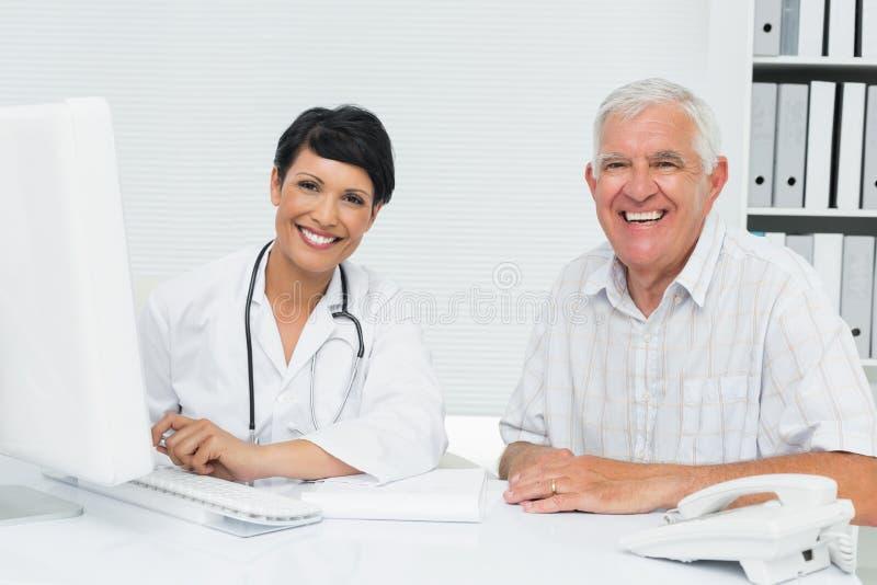 Portrait d'un docteur féminin heureux avec le patient masculin images stock