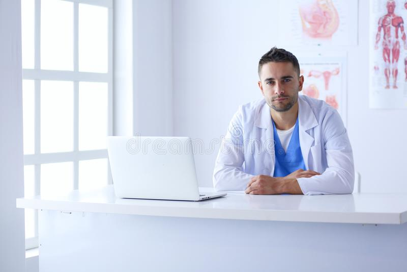 Portrait d'un docteur masculin avec l'ordinateur portable se reposant au bureau dans le bureau médical image stock
