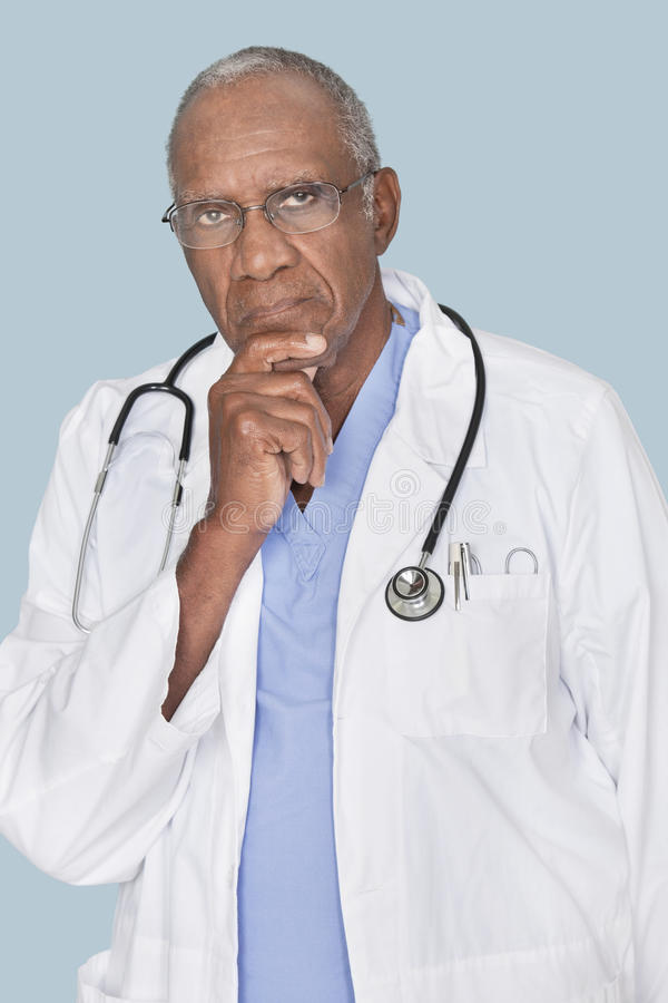 Portrait d'un docteur sérieux d'Afro-américain avec la main sur le menton au-dessus du fond bleu-clair images libres de droits