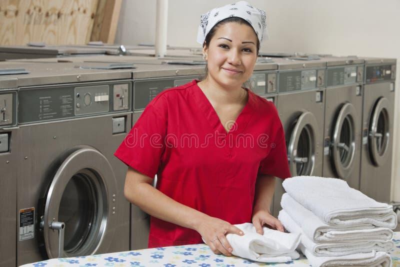 Portrait d'un employé féminin hispanique avec la serviette dans la laverie automatique image libre de droits