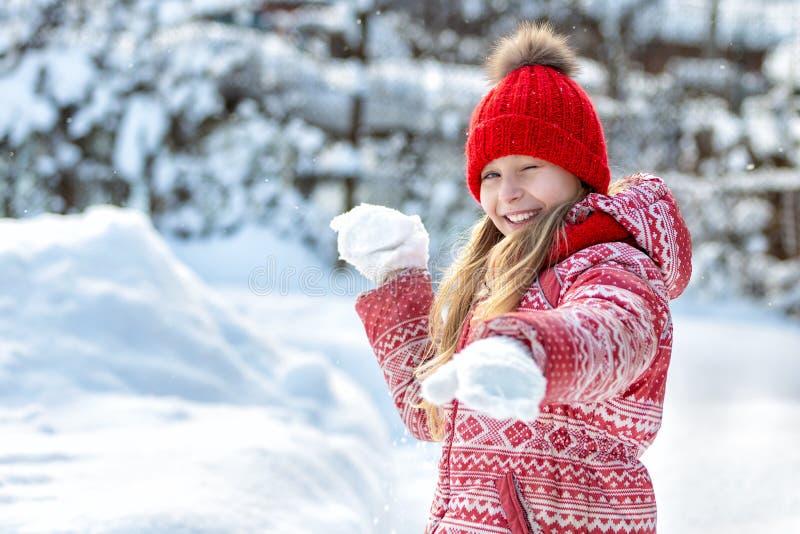 Portrait d'un enfant heureux pendant l'hiver Fille gaie dehors Jeu de Snowball photos stock