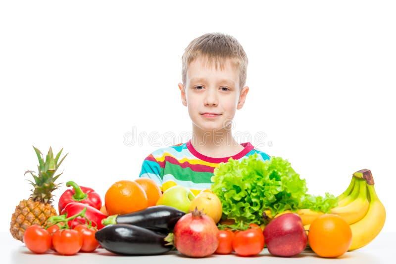 Portrait d'un garçon à la table avec une pile des légumes frais et des fruits d'isolement photographie stock