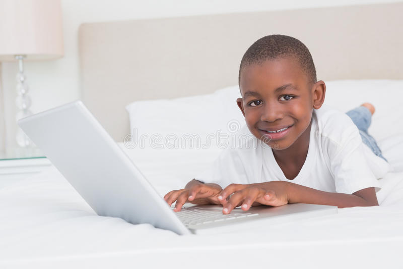 Download Portrait D'un Garçon Assez Petit à L'aide De L'ordinateur Portable Dans Le Lit Photo stock - Image du heureux, domicile: 56484748