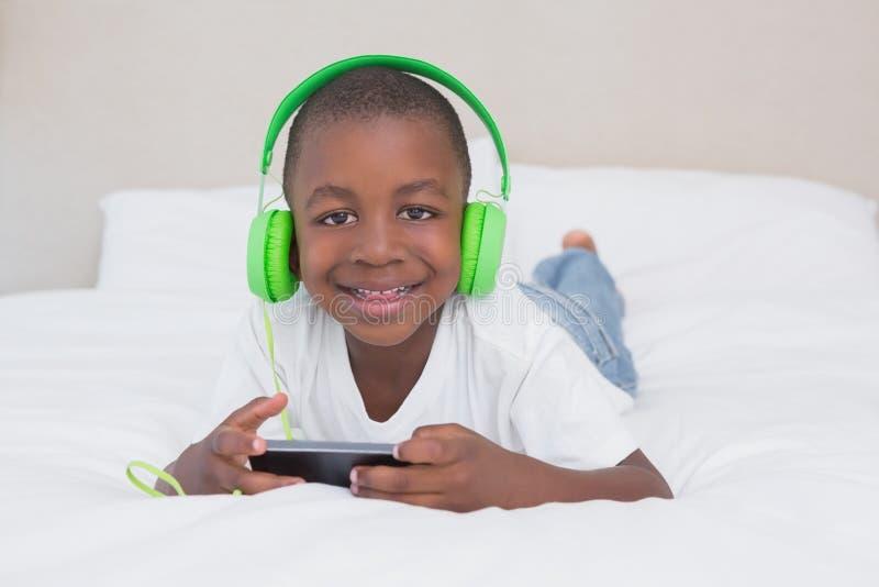 Download Portrait D'un Garçon Assez Petit à L'aide Du Smartphone Et De La Musique De écoute Dans Le Lit Image stock - Image du vêtement, personne: 56485407