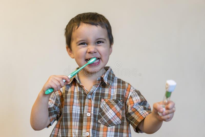 portrait d'un garçon blond de beau Caucasien mignon avec une brosse à dents Dents de brossage de petit garçon et sourire tout en  image stock