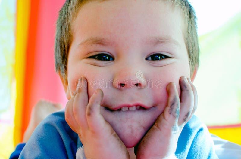 Portrait d'un garçon d'enfant en bas âge avec le visage et les mains sales images libres de droits